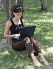 female student sitting under tree working with laptop