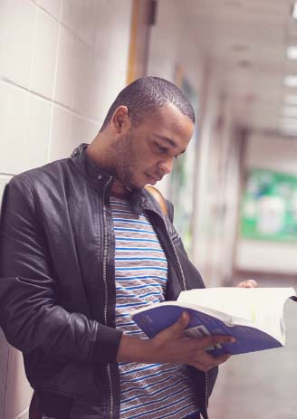 student resources man reading handbook in hallway