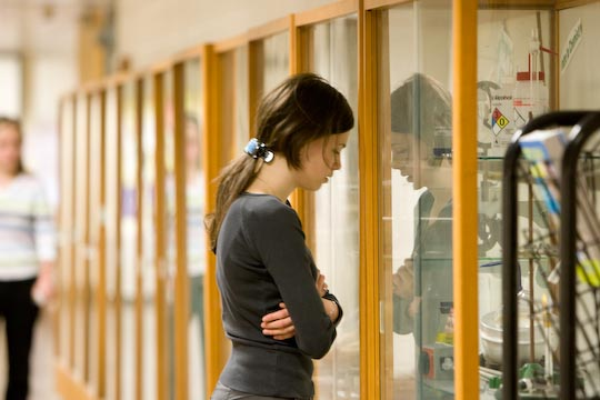 troubled student with head resting against trophy case